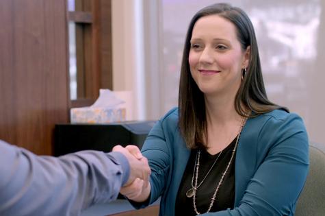 financial advisor natalie berning shaking hands with man across her desk