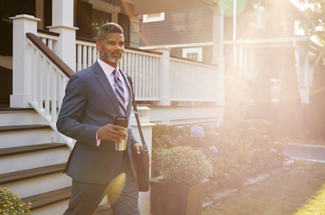 Charitable Foundation and Endowment Planning_professional man walking down in front of his house holding a cup of coffee