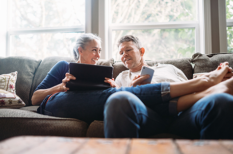 Mature Couple Relaxing with Tablet and Smartphone