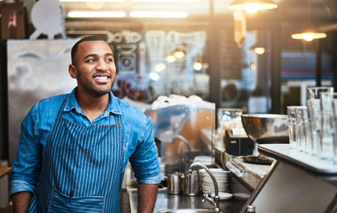 Young man behind the counter at a small business franchise location.