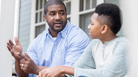 Caring mid African American father gestures as he gives advice to his preteen son. They are looking at one another. They are sitting on the front porch of their home.