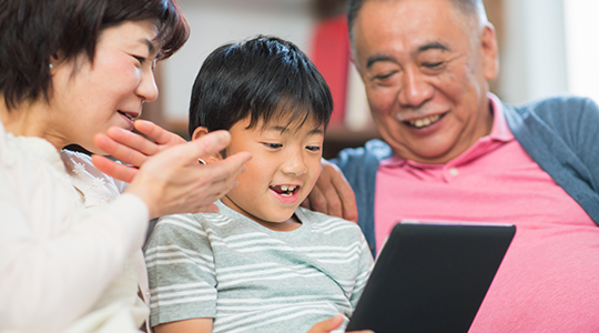 Young boy using his digital tablet whilst his grandparents watch and offer encouragement.