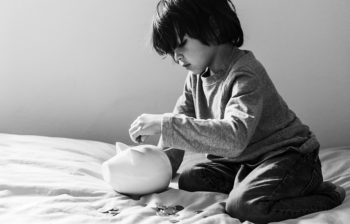 Young boy putting money in a white piggy bank