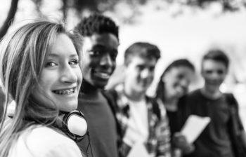 Teenage girl wearing headphones smiles with her friends