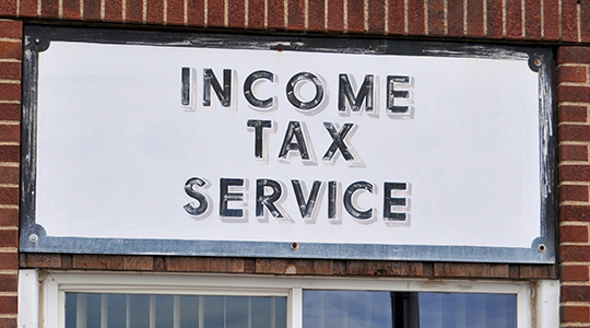 An old and worn sign for Income Tax Service