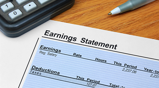 An itemized earnings statement showing earnings and deductions, on a desk with a calculator and pen.