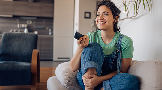 Young woman sitting on the sofa, watching TV at home and enjoying.