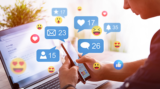 Like and share social media. Hands holding smartphone with social media network icons.