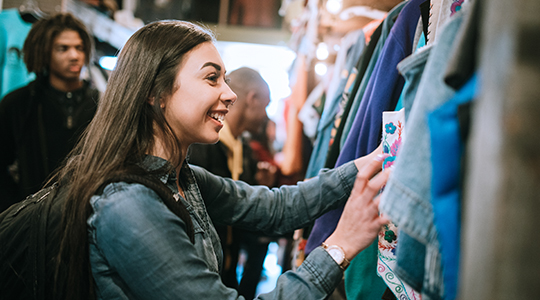 A smiling group of young adults have fun shopping for retro and vintage clothing styles.