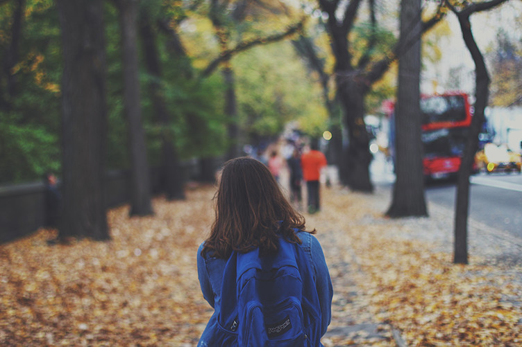 Youth Villages Oregon: Supporting Youth Aging out of the Foster Care System_Young girl with backpack walking through leaves