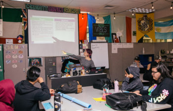 Teacher points out topic on overhead projection screen while students look on in Skyview High School classroom