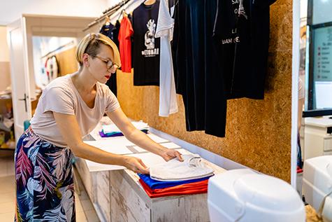 Business owner folding T-shirt in her digital printing workshop