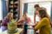 Family huddles around kitchen table with mom and dad reviewing finances on laptop and son and daughter working on school work
