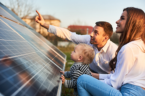 Young woman with a kid and a man in the sun rays look at the solar panels.
