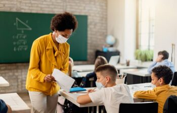 masked teacher shares paper with masked student