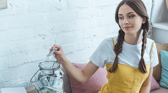 teen girl putting dollar banknote into saving glass jar