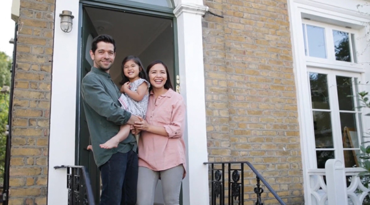 family stands at the doorstep of their new home