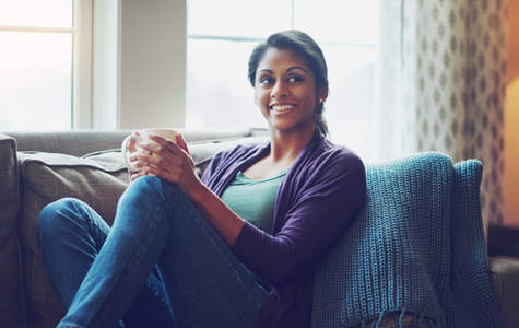 Young woman sitting on her couch enjoying a cup of coffee