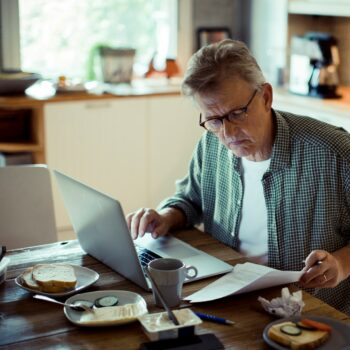 Fixed-Income Investors Low Interest Rates_mature man reviewing documents in front of laptop