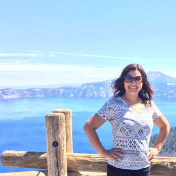 Spotlight Interview with Marlen Mendoza-Marlen posing in front of a scenic mountain and lake view in the pacific northwest crater lake