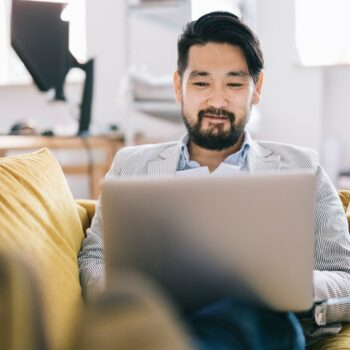 Traits of a Great Financial Advisor-japanese man consideing finances while sitting on yellow couch and typing on computer