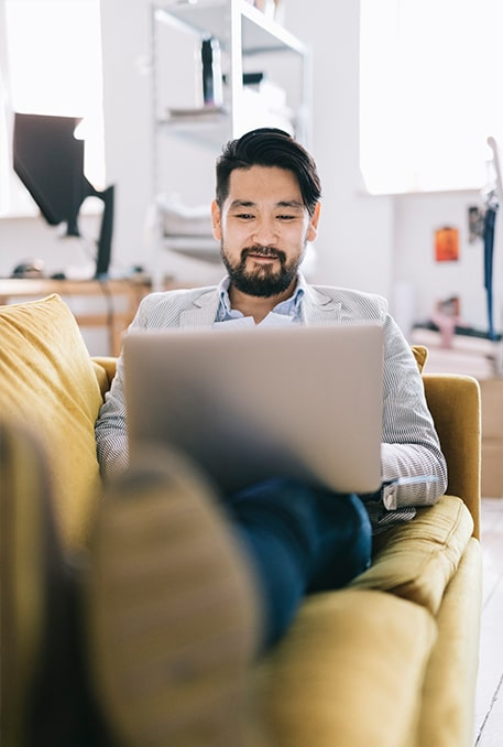 Traits of a Great Financial Advisor-pleased japanese man researching advisors from the couch