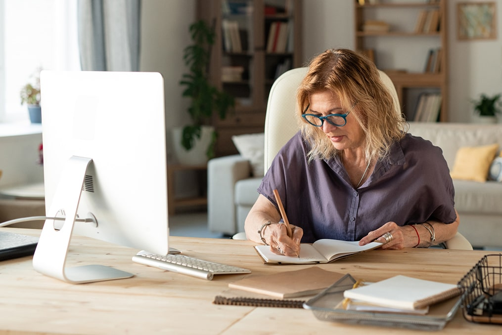 What Should You Ask a Financial Advisor-mature woman taking notes at her desk