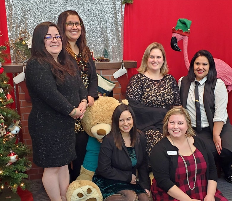 spotlight interview with Maritza Rich-maritza with her OnPoint team near the xmas tree