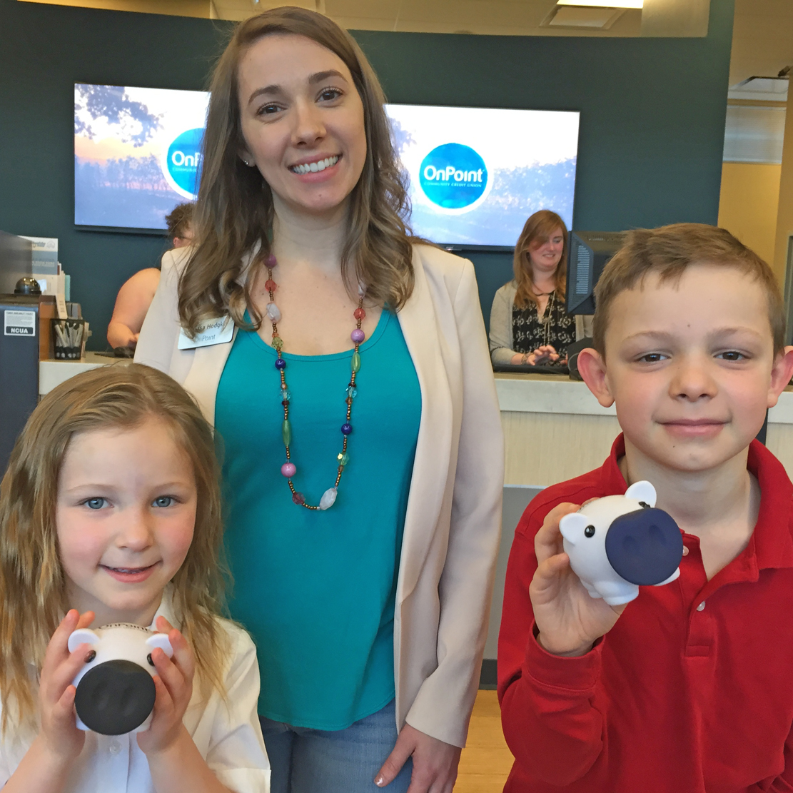Mother with her two children at an OnPoint branch - each child has an OnPoint Piggy Bank