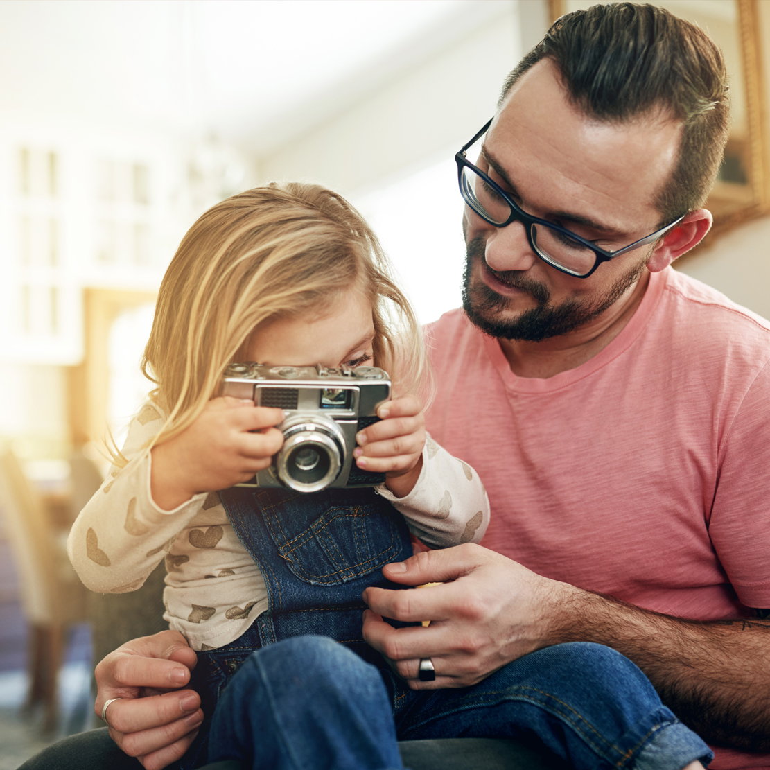 daughter sitting on fathers lap holding a camera and taking a picture