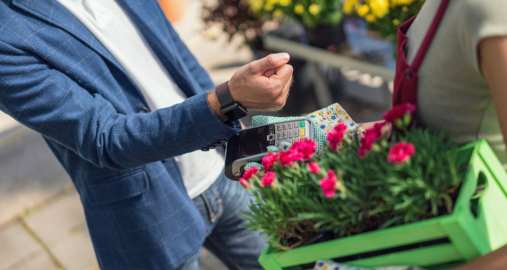 The Pros and Cons of Popular Payment Methods_man using contactless payment at local flower shop