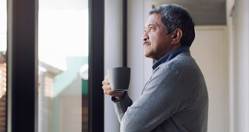 What to Do If You're Not on Track for Retirement_senior drinking coffee while looking out a window