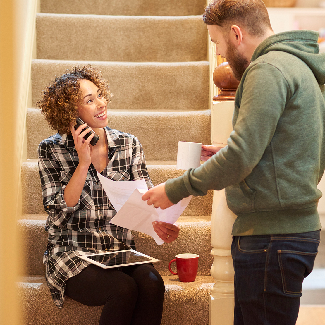 couple standing near their stairs and looking over some paperwork while she makes a phone call