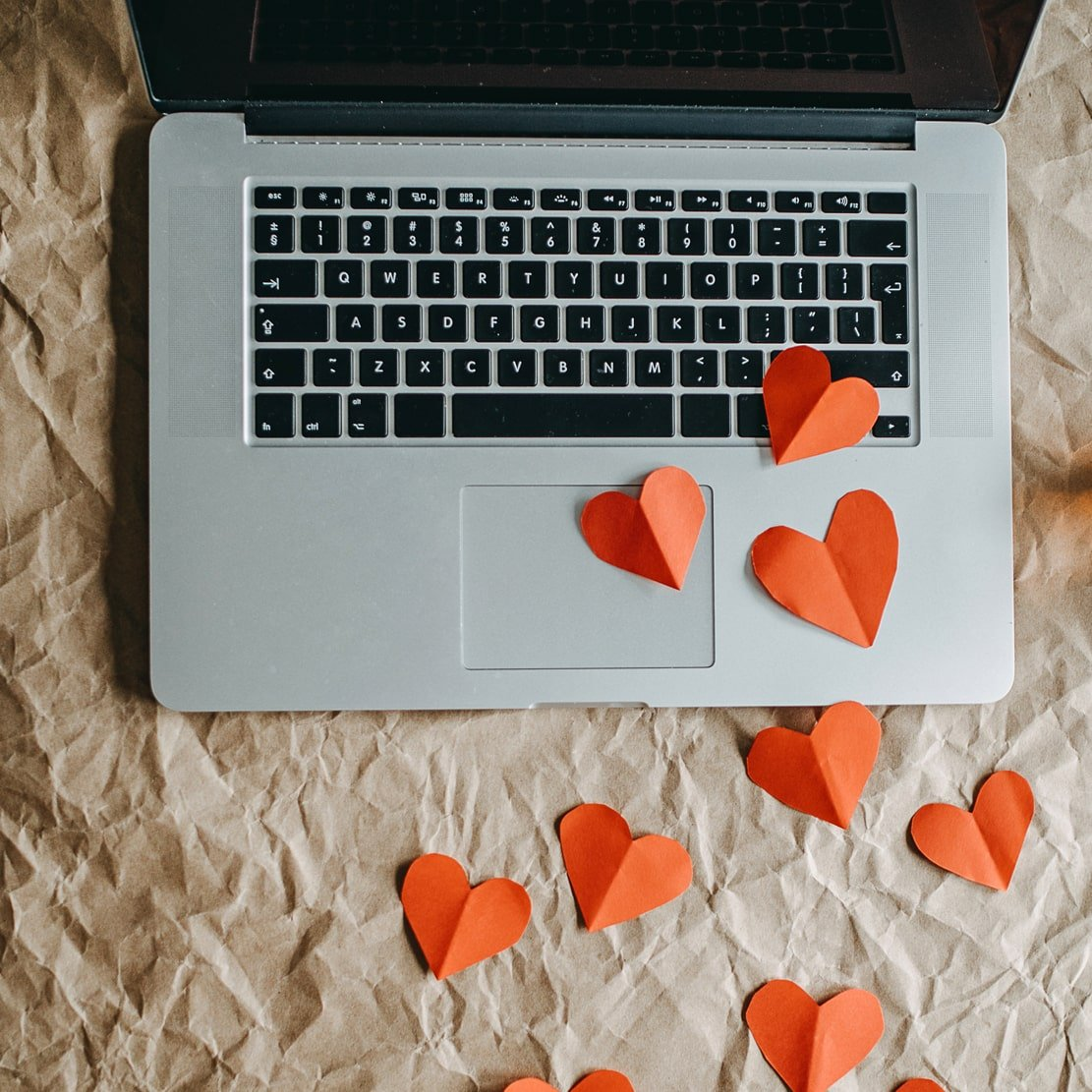 Paper hearts leading to a laptop_don't fall prey to a sweetheart scam