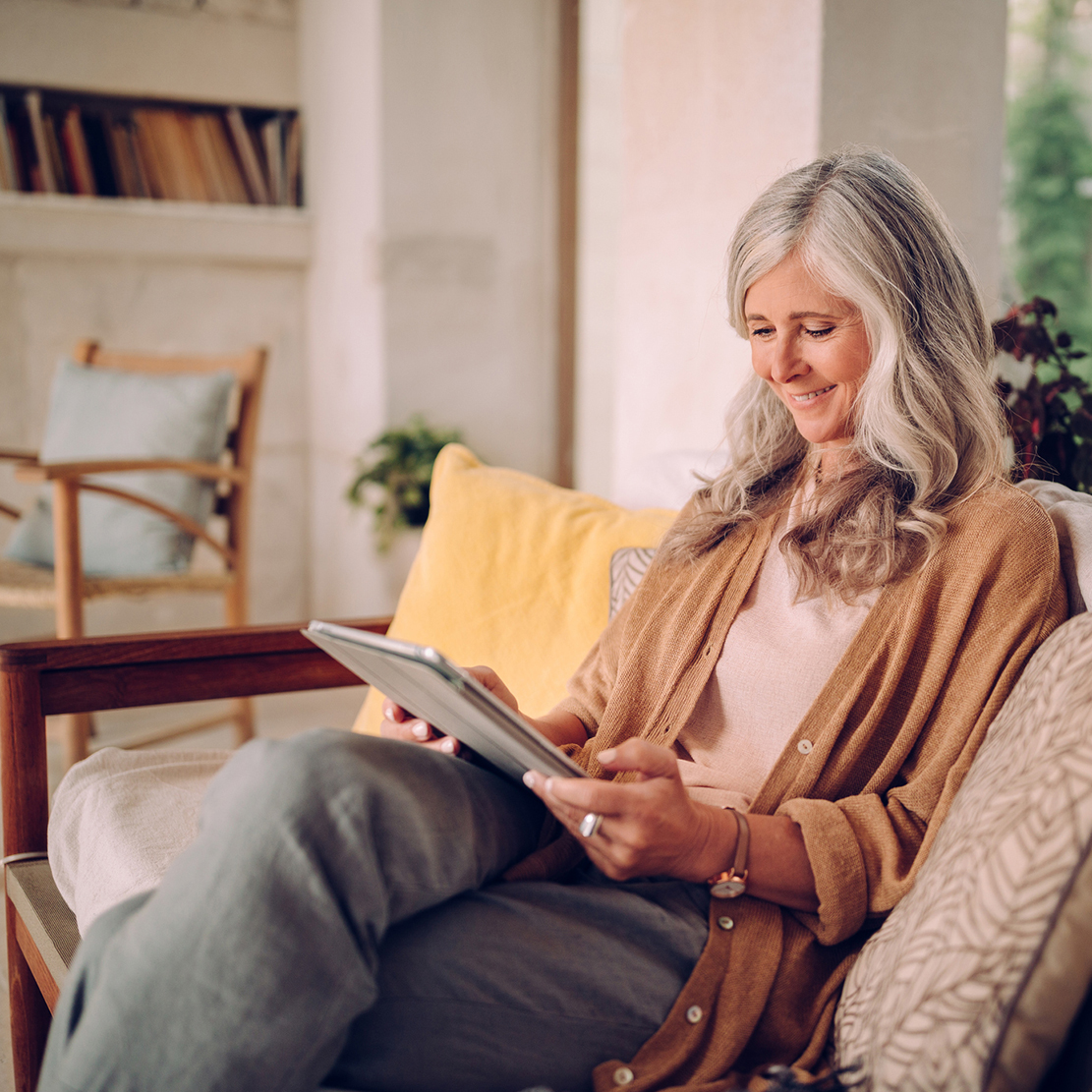 senior woman sitting on her couch looking at her tablet