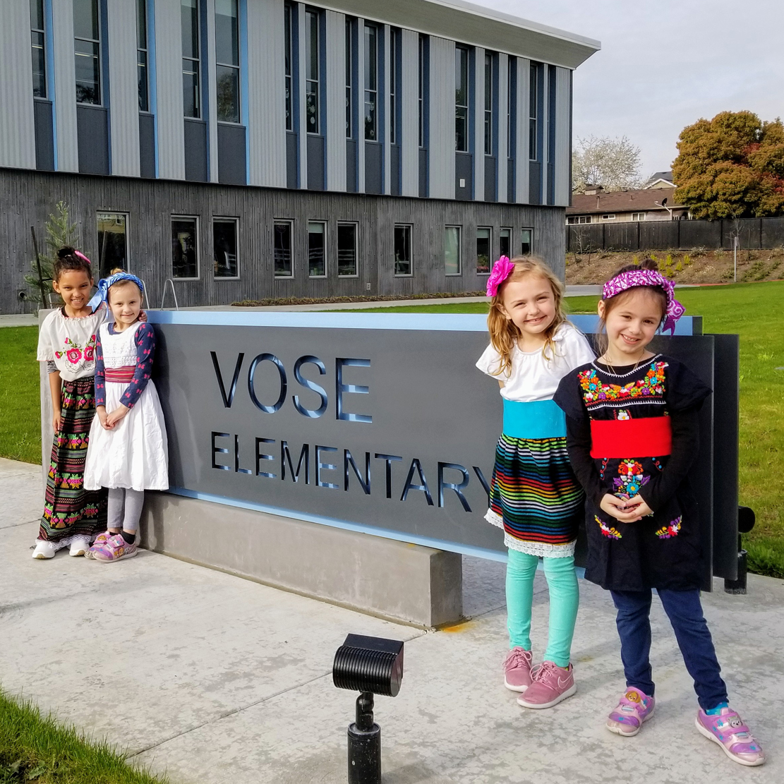 students outside of vose elementary school standing near the school sign