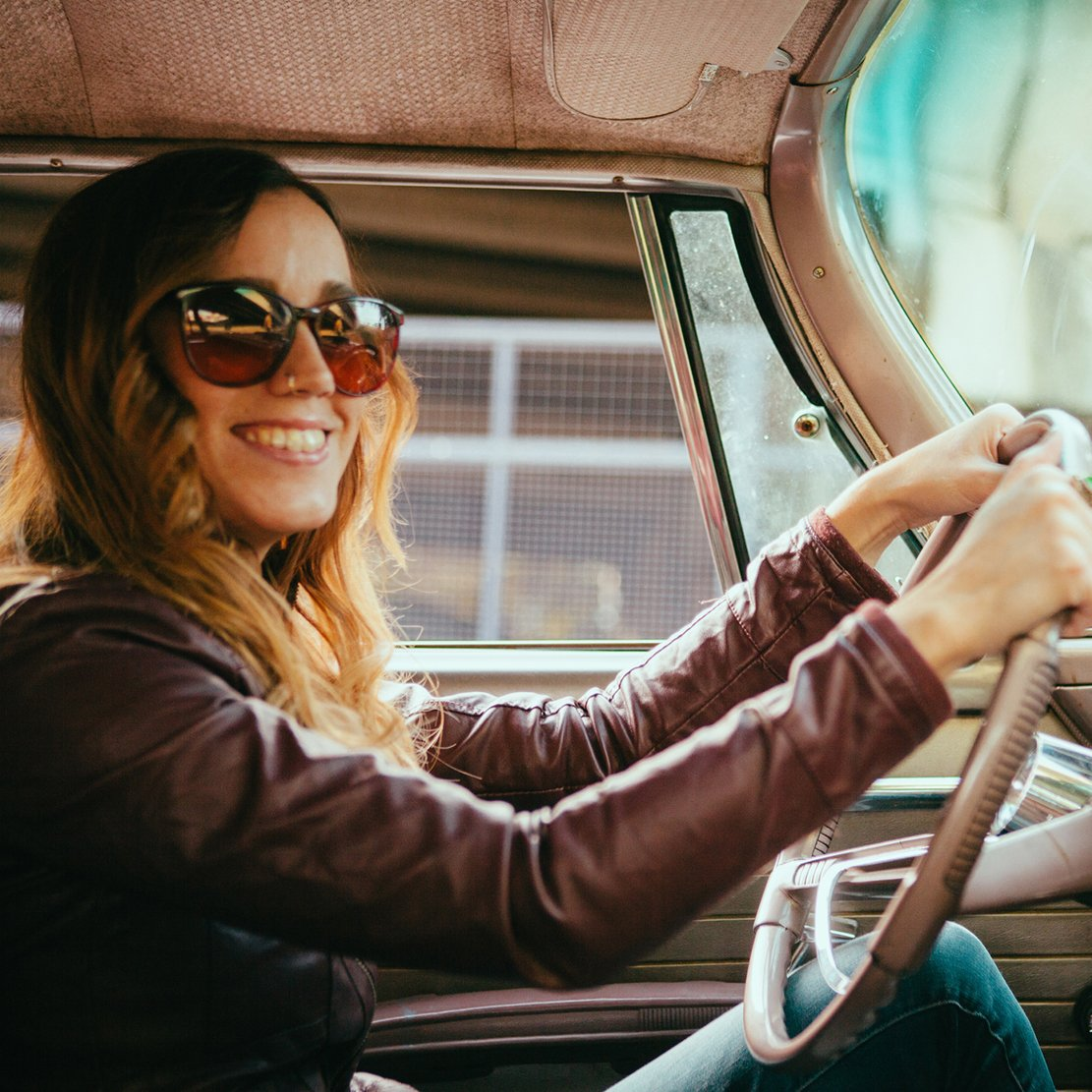 trendy woman sitting behind the wheel of a classic car
