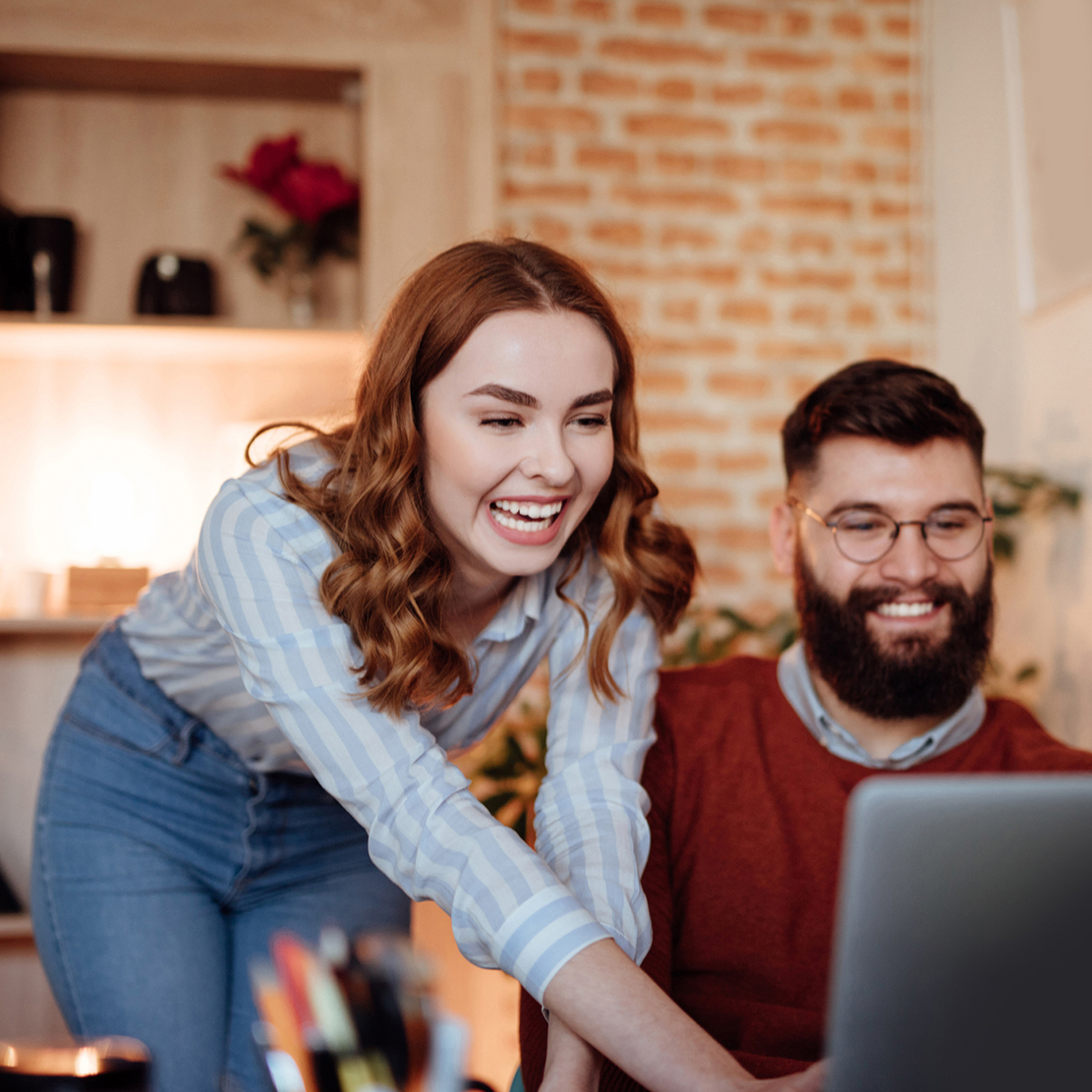 woman and man working together on their budget strategy she's pointing over his shoulder at their laptop