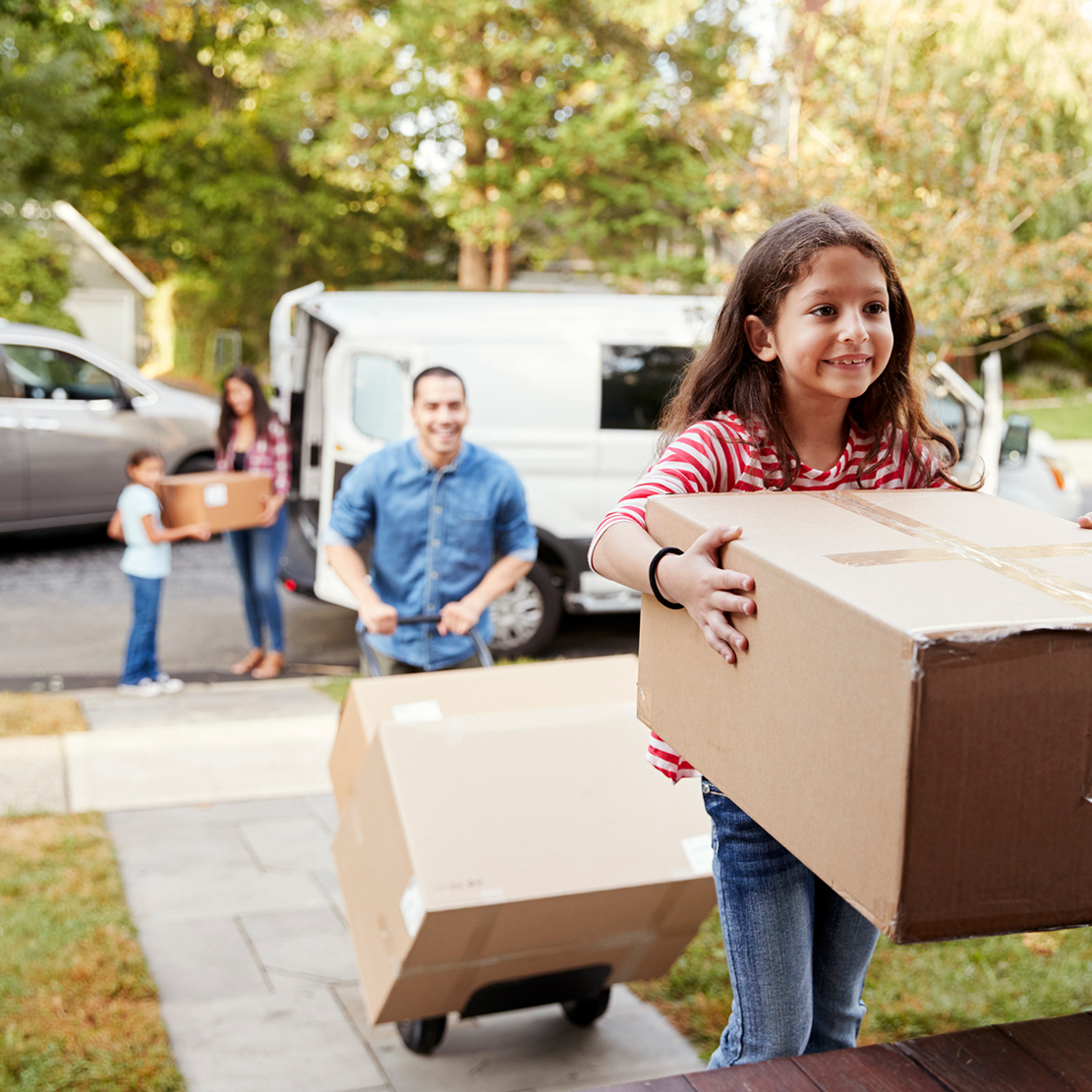 young girl carrying a box into her new home - with the rest of family unloading boxes in the background