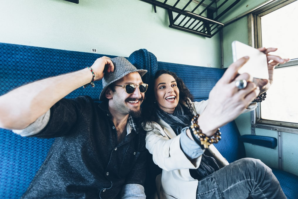 woman taking a selfie with her new partner while travelling on a train_how to avoid a sweetheart scam