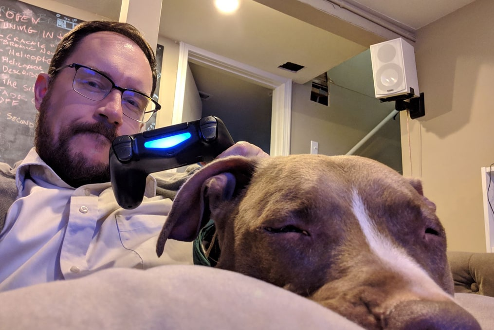 David Biastock playing video games at home and relaxing with his dog