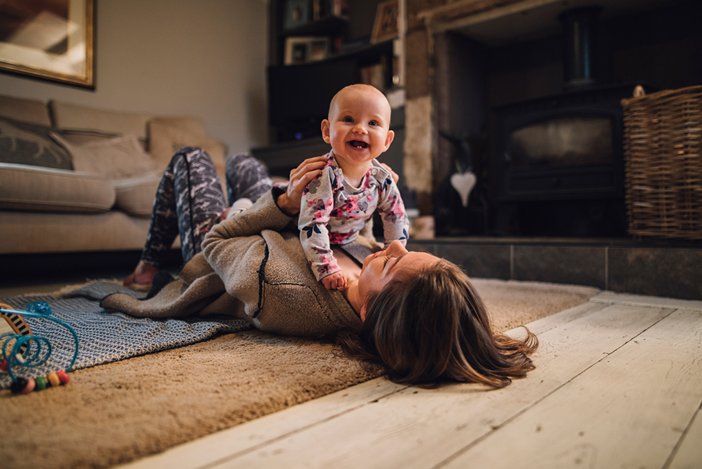 baby laughing while laying with mom on the floor