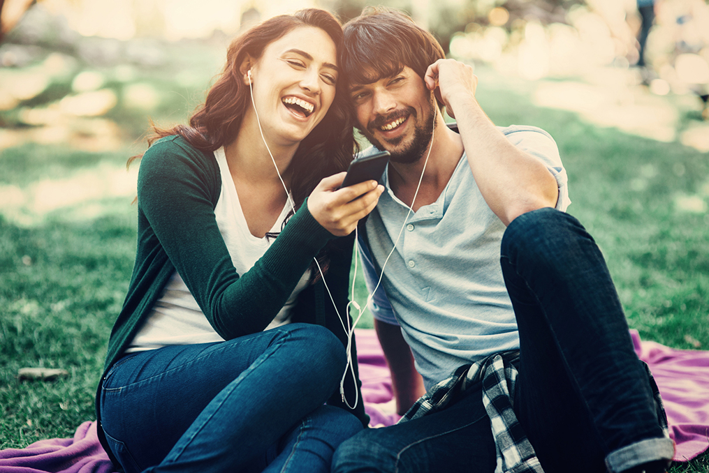 couple leaning close listening to music at the park while sharing a pair of headphones
