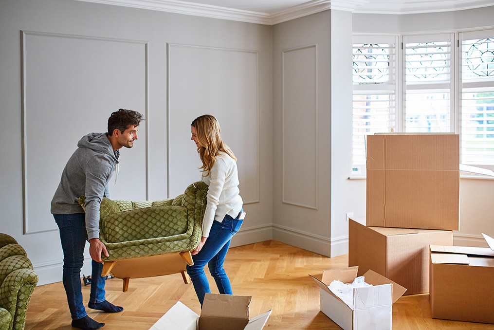 couple moving into their new home placing their modern green chair in the living room