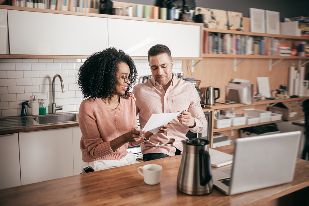 couple sitting in their kitchen looking over paperwork and doing research on a new home purchase