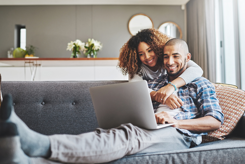 couple smiling on the couch with legs crossed while reviewing their credit report