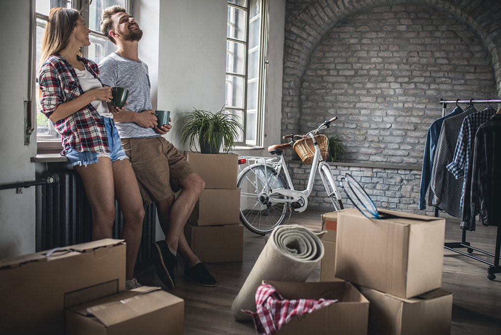 couple standing in their living room surrounded by boxes with a lot of unpacking to do