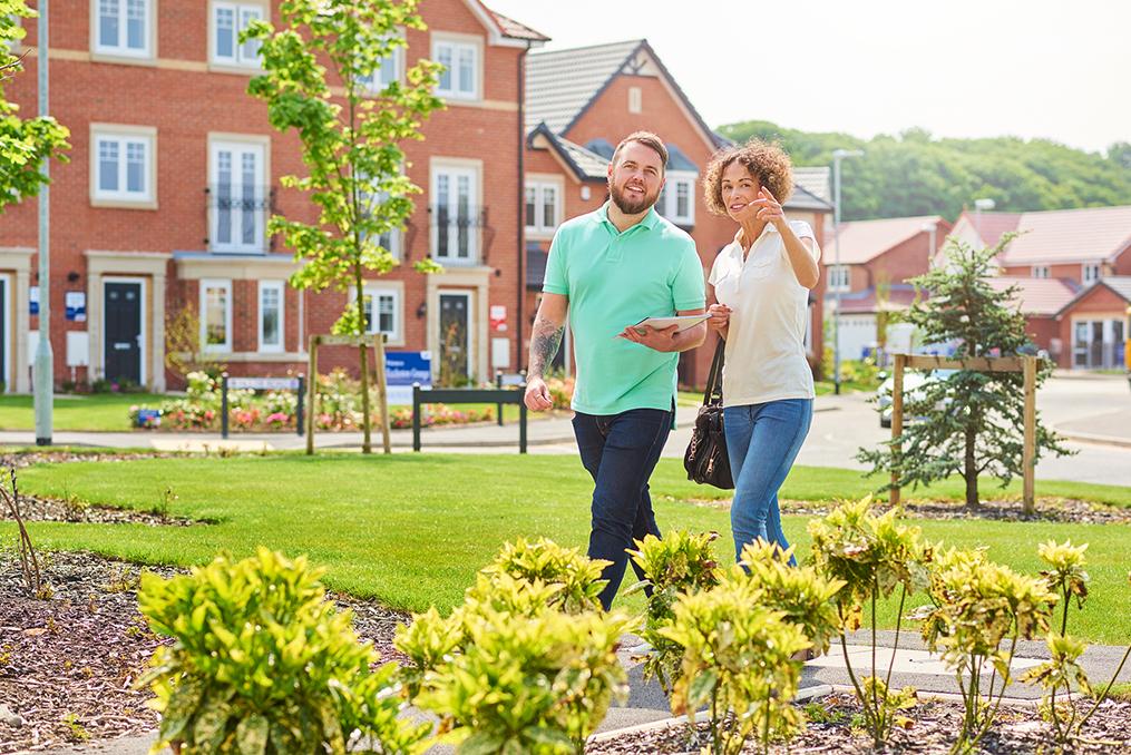 couple walking through a neighborhood on a sunny day house shopping