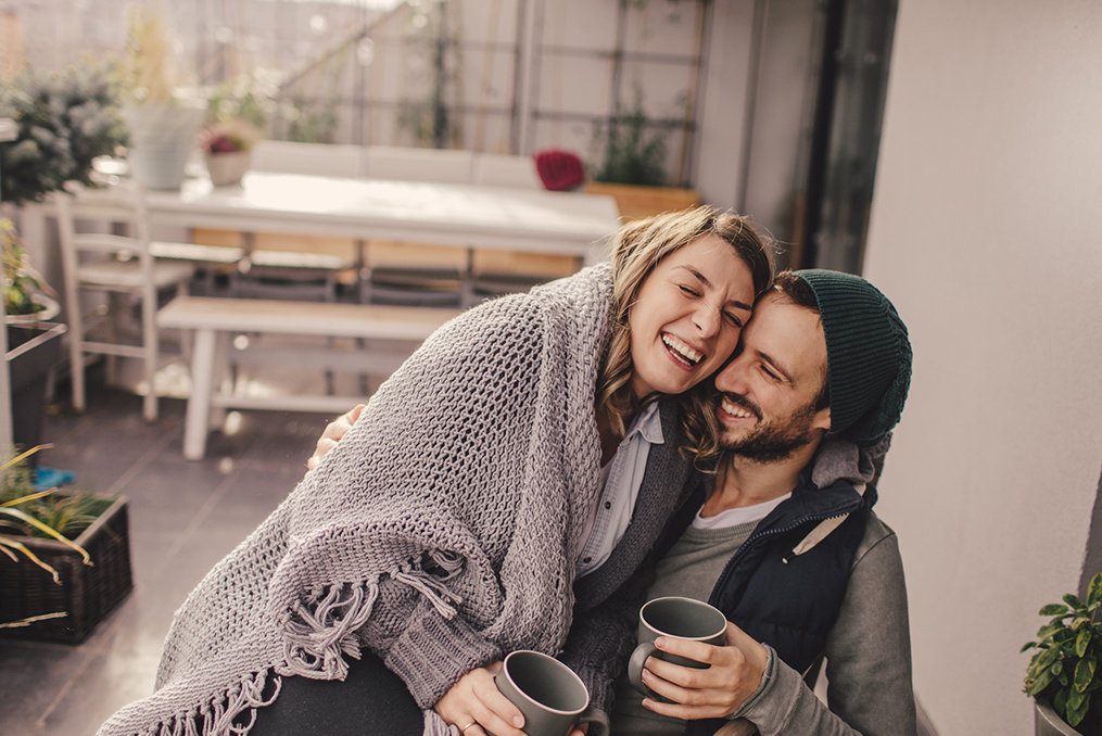 couple warming up with blankets and coffee at home