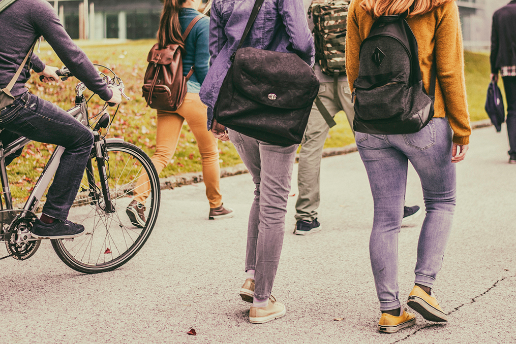 group of students walking and biking through a college campus